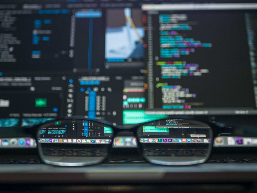 Glasses on a desk with computer code in the background